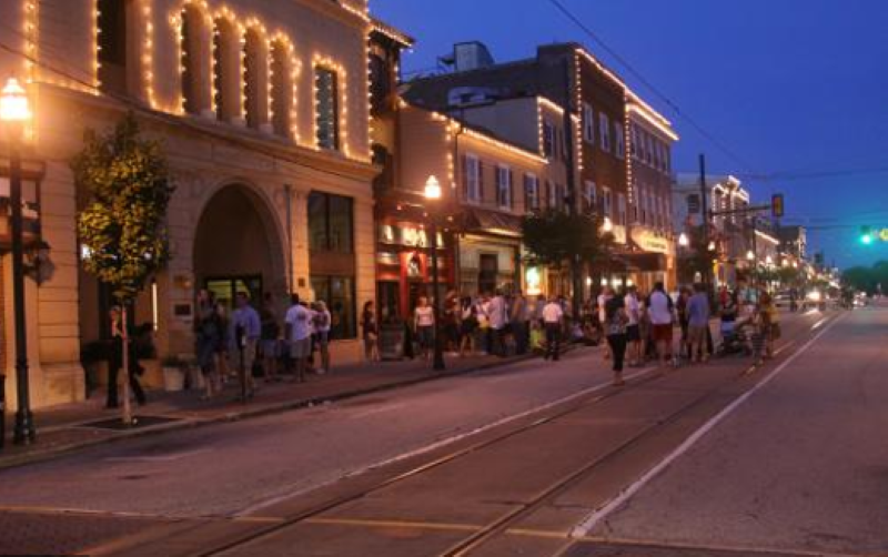 Night time scene of Media with the older buildings outlined in white twinkle lights and people mingling in the street and sidewalk