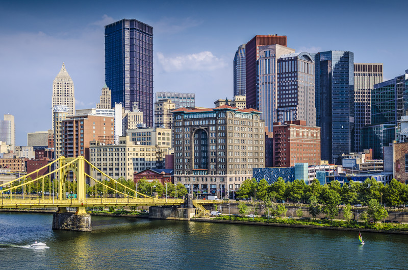 Top places to retire in Pennsylvania Daytime photo of Pittsburgh, Pennsylvania showing the yellow bridge over the Allegheny River and with downtown Pittsburgh as the backdrop
