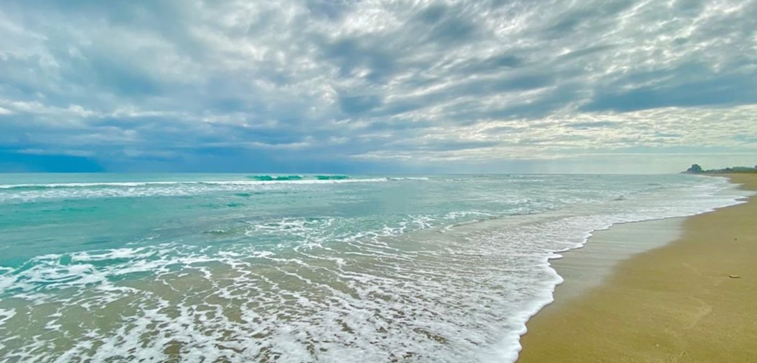 Sandy beach of Port St Lucie and the aqua ocean with a blue sky with soft cloud cover backdrop