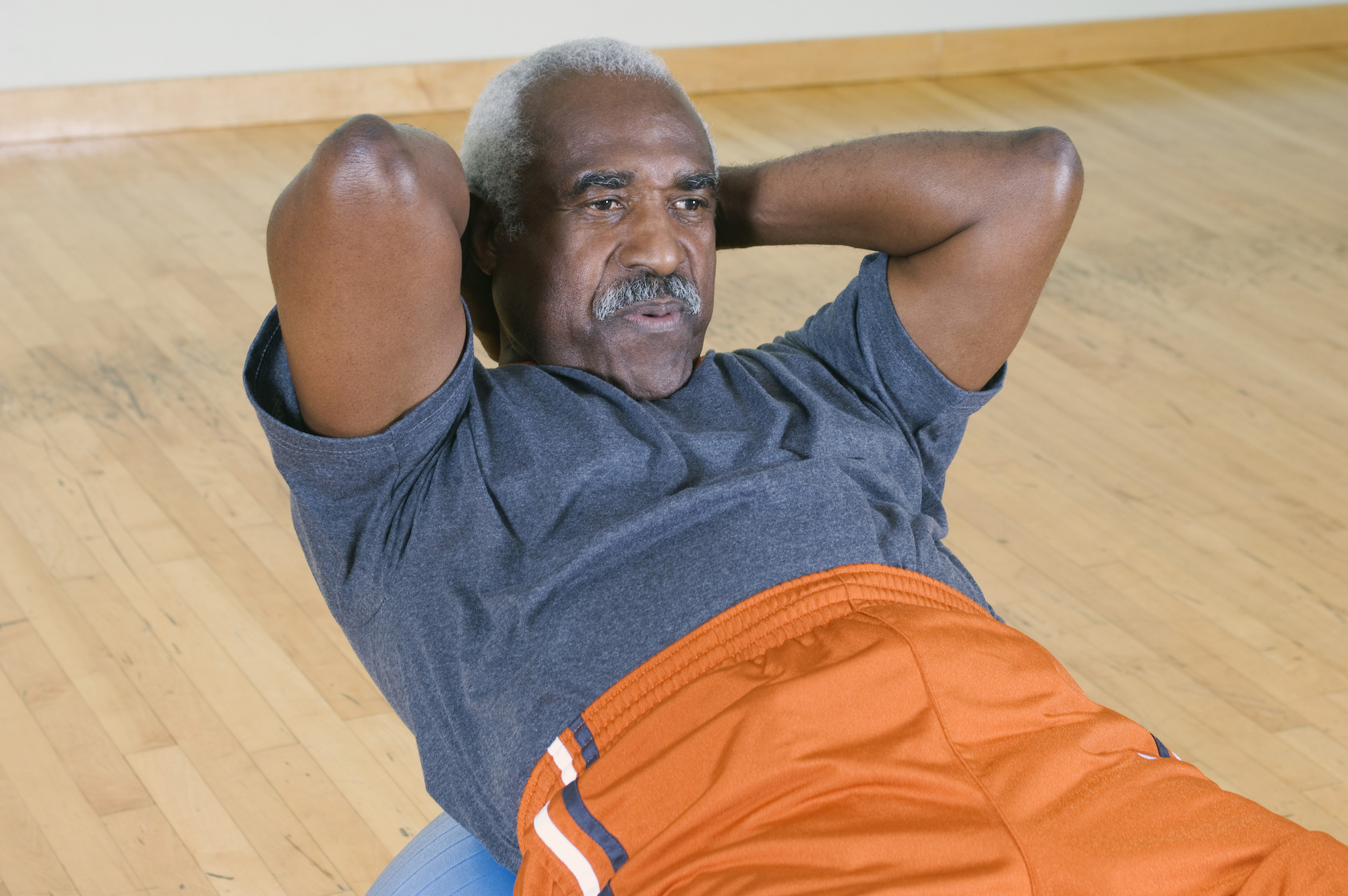 african american man doing situps on a pilates ball at home
