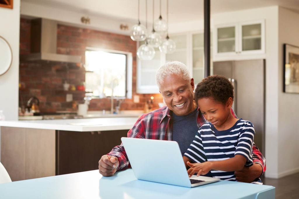african american senior man sitting with grandson in kitchn playing on laptop