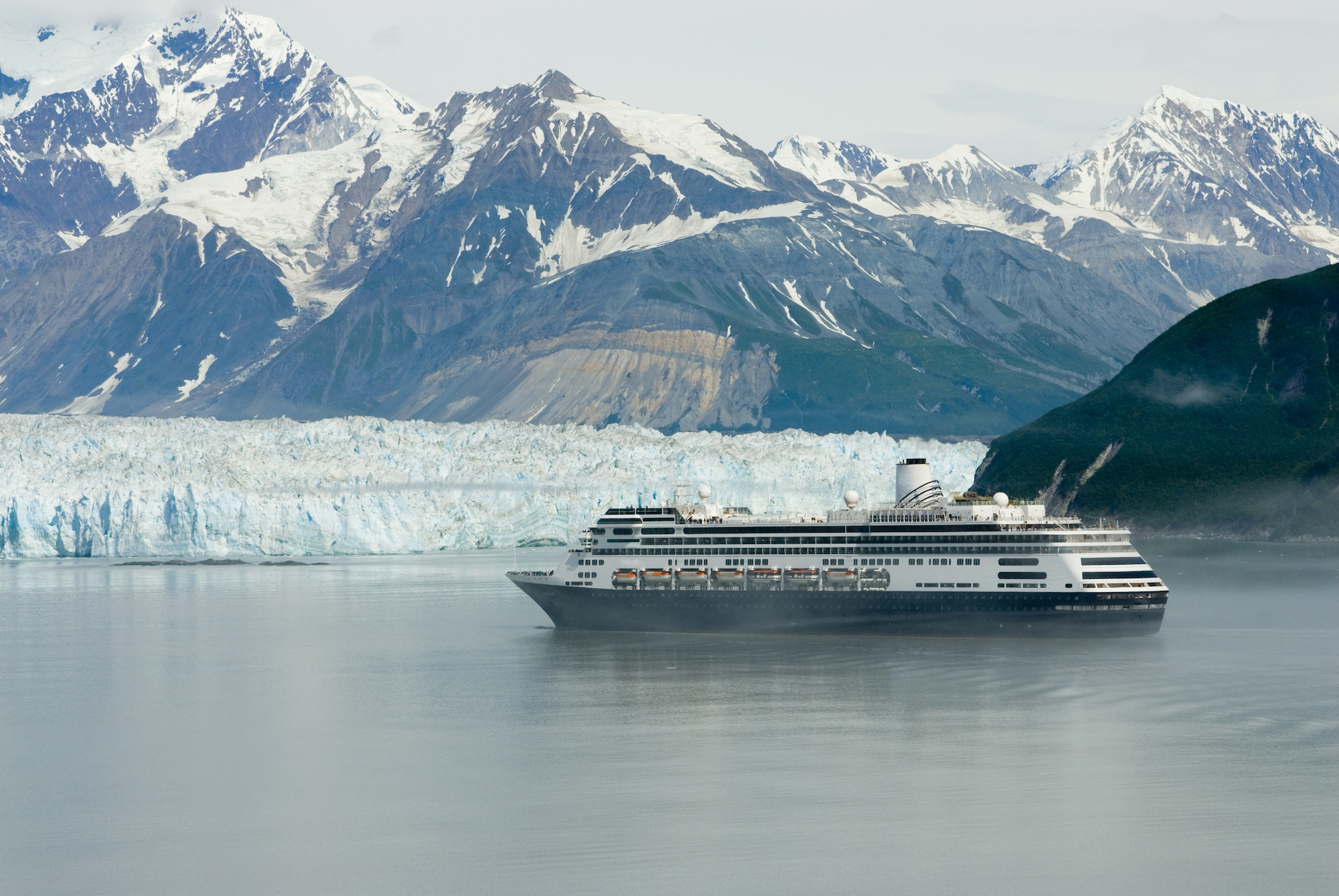 alaskan cruise ship with glacier and mountains in the background