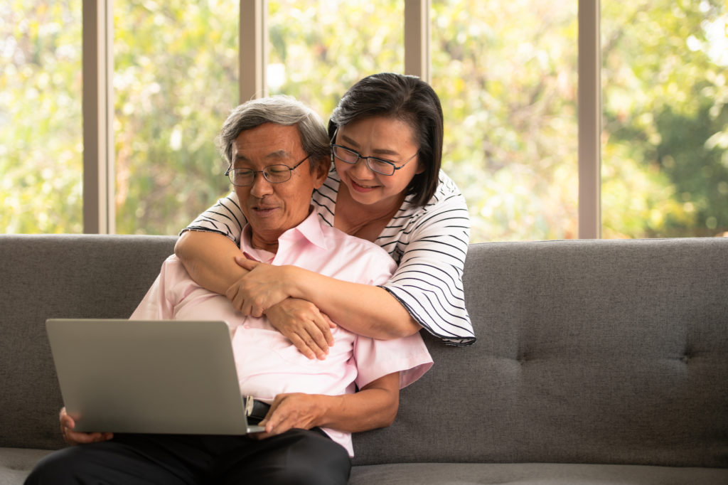 asian senior couple looking at a laptop computer sitting on couch