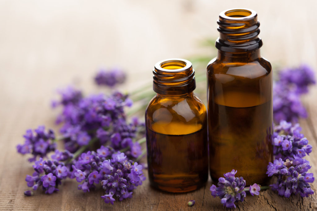 There are two unopened bottles of essential oils and some lavender flowers.