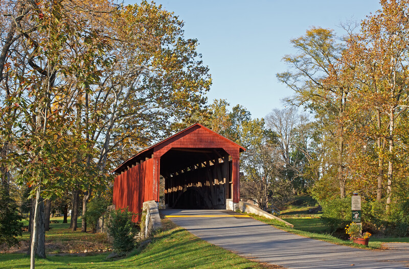 Red barn style bridge heading into Lancaster, surrounded by trees