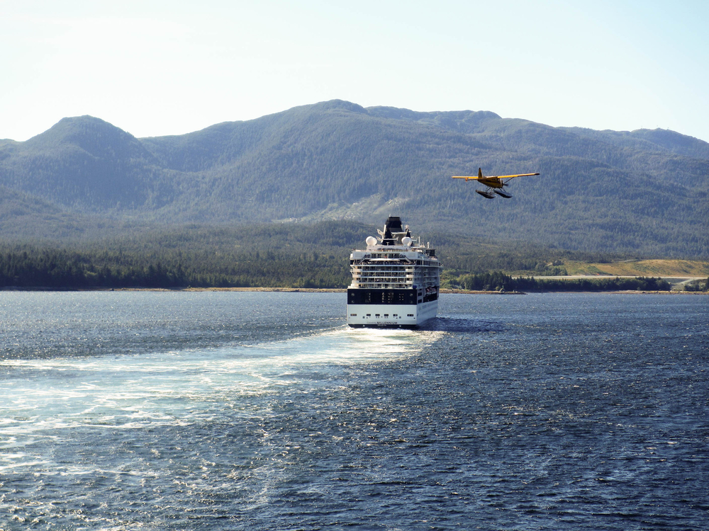 A float plane returning from a sightseeing trip flies past the Celebrity Millennium cruise ship as it departs the town