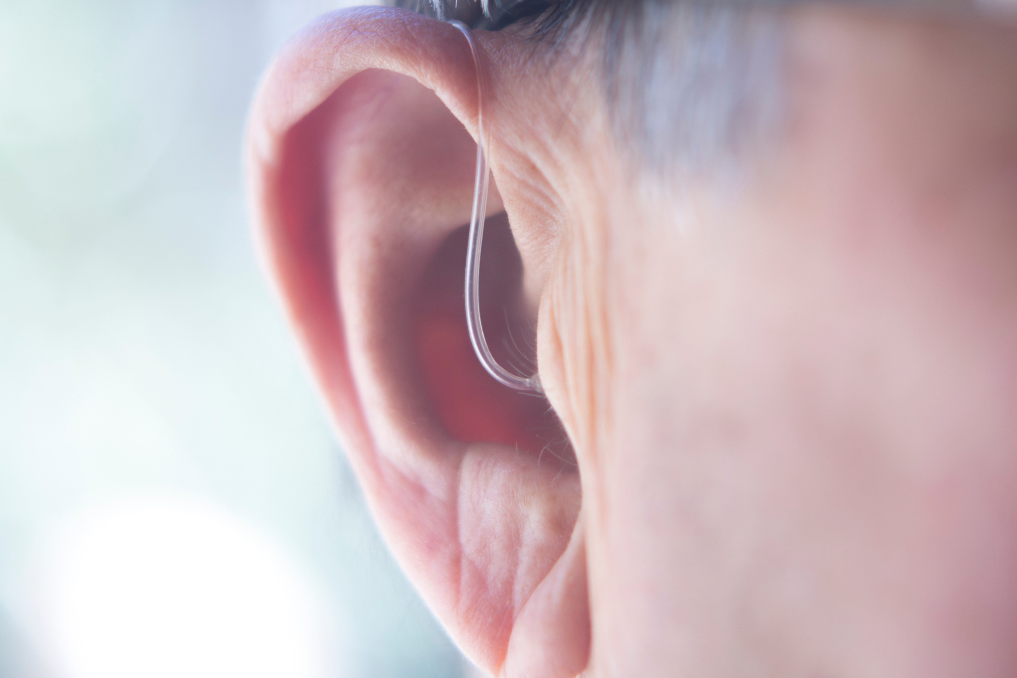 closeup photo of ear of elderly man with hearing aid inserted