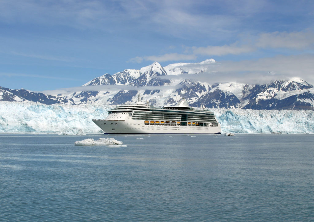 A cruise ship with icy mountains and glaciers in the background