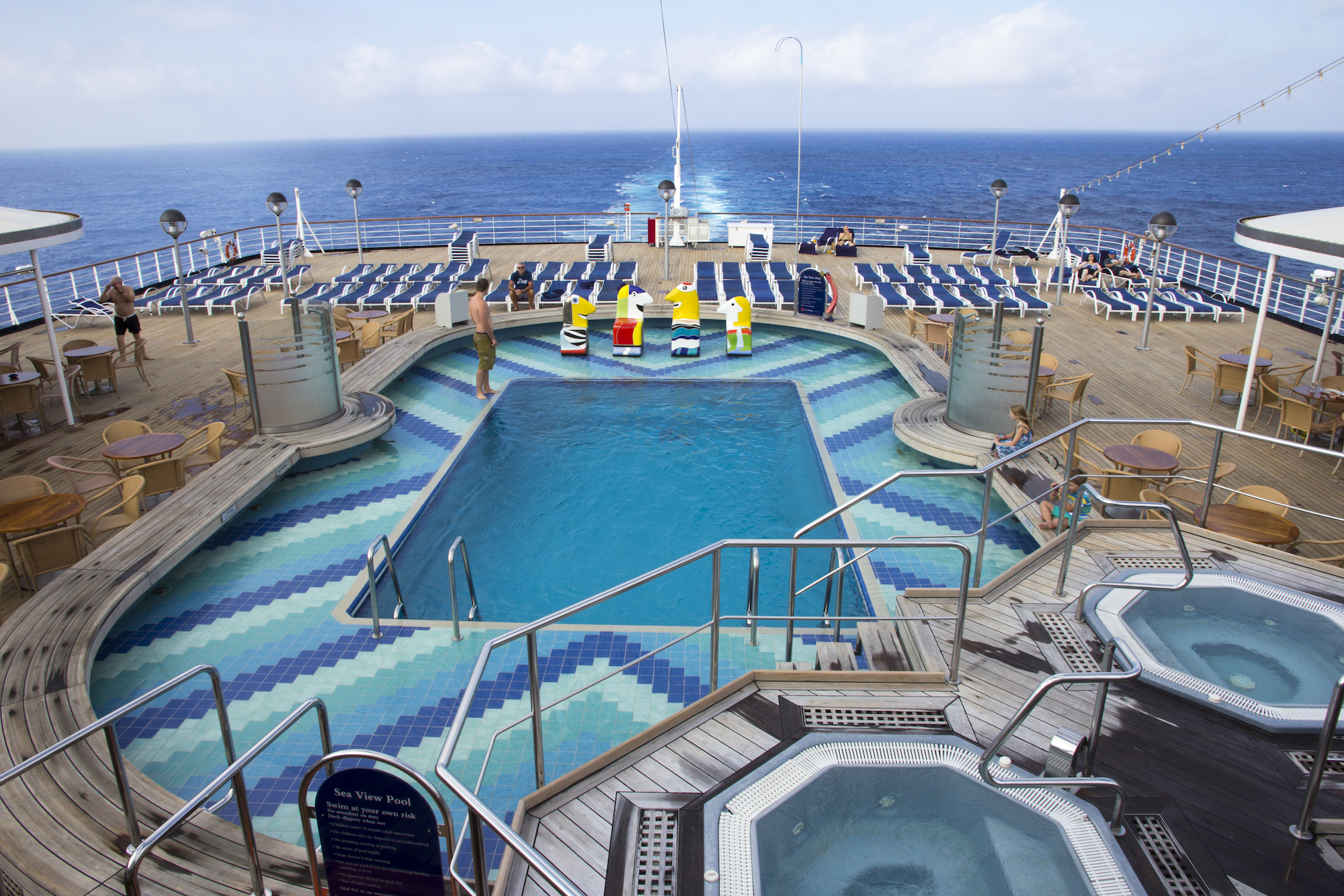 deck of holland america cruise ship with pool and ocean in background