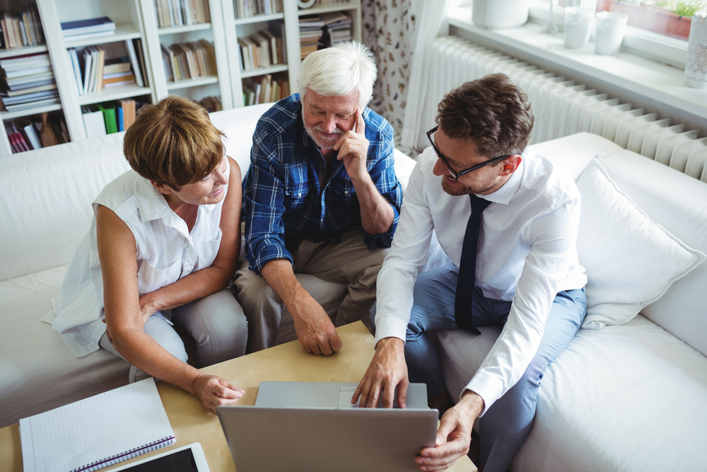 elderly couple sitting with estate planning agent going over numbers on a laptop