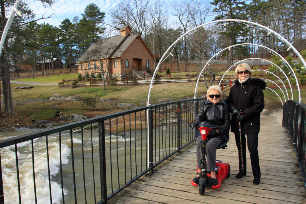 elderly woman on a mobility scooter with her caretaker standing on a wooden bridge