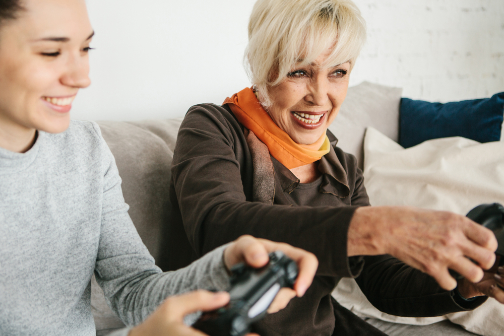 elderly woman playing video games with granddaughter