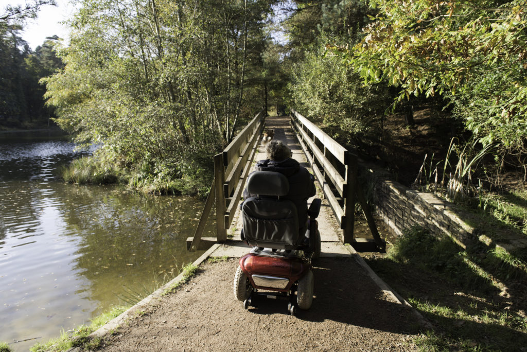 elderly woman riding mobility scooter crossing a bridget over water on a walking path