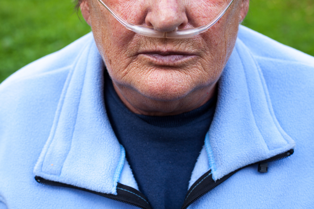 elderly woman with portable oxygen machine and nasal catheter