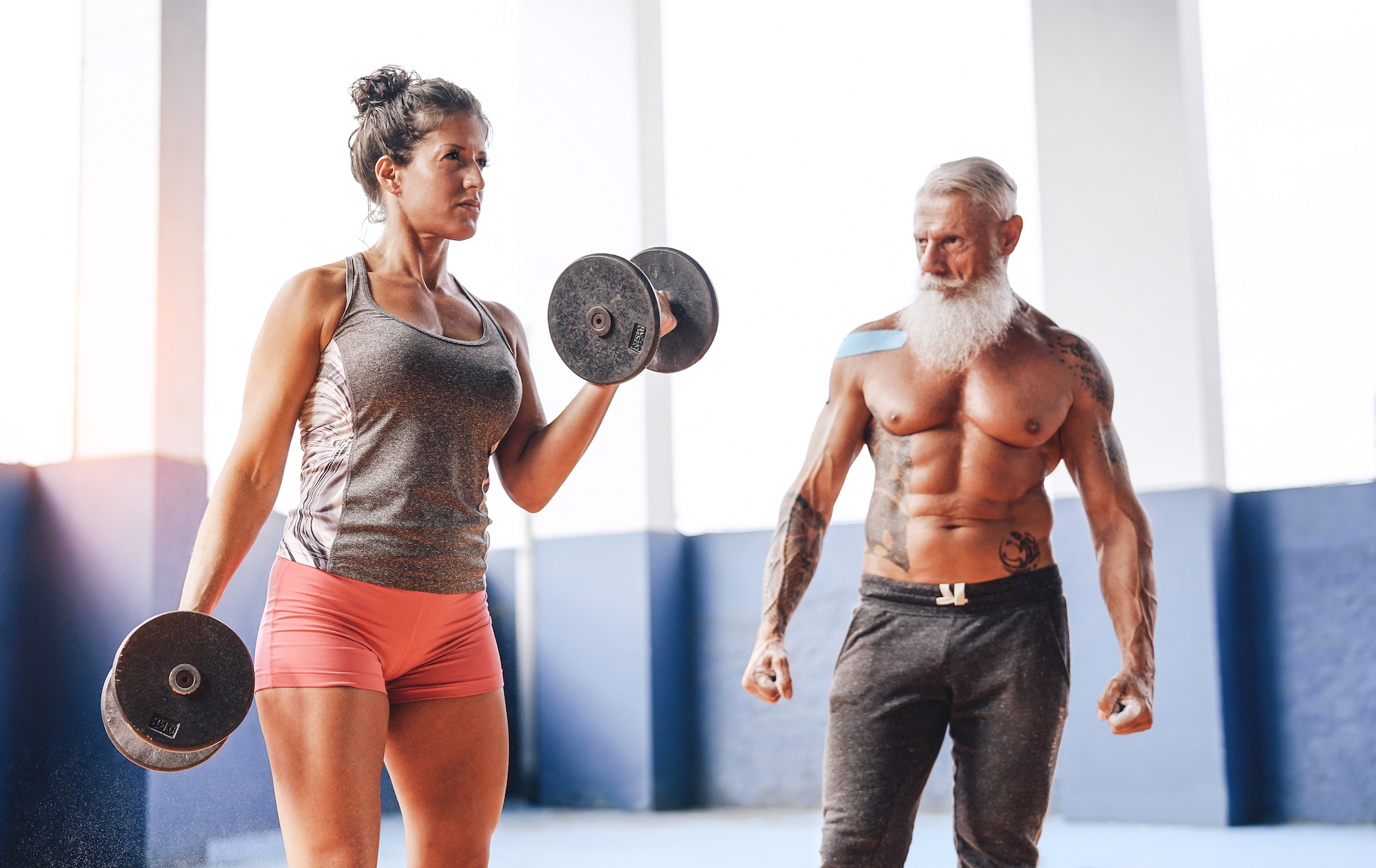 fit senior man and woman with dumbells doing curls