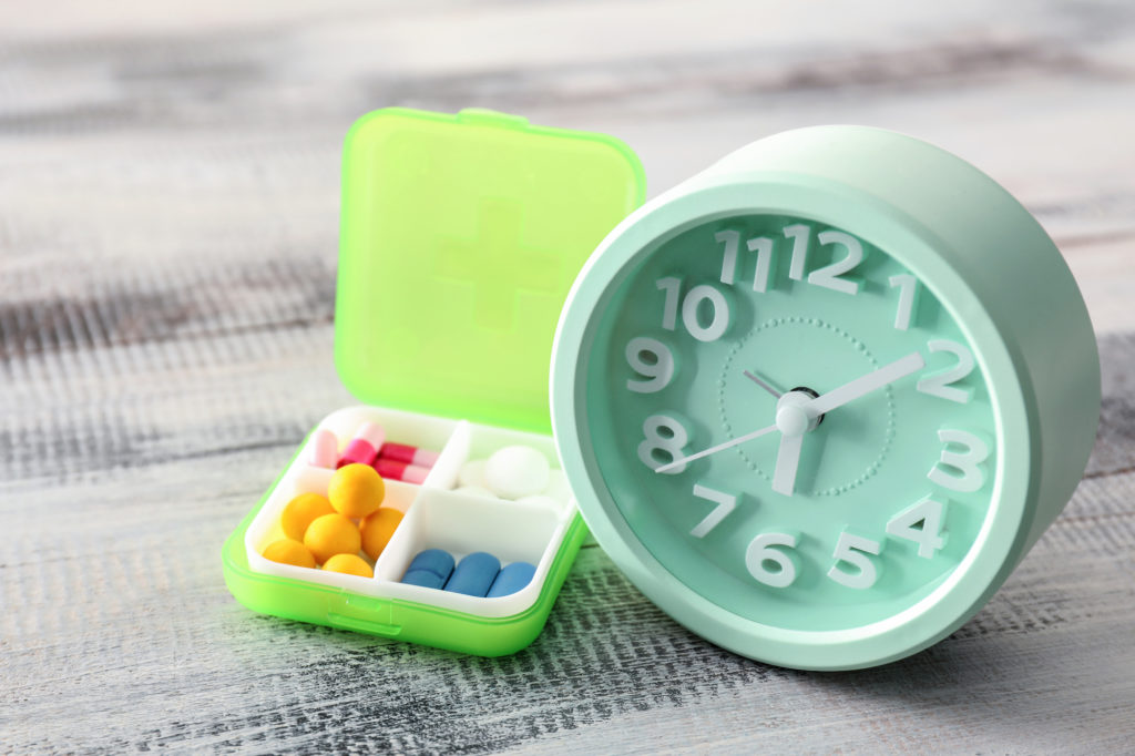 green clock with small pill box that has four compartments and different colored pills inside