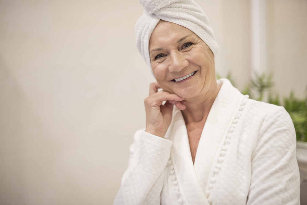 happy elderly woman in bath robe with hair wrapped in towel