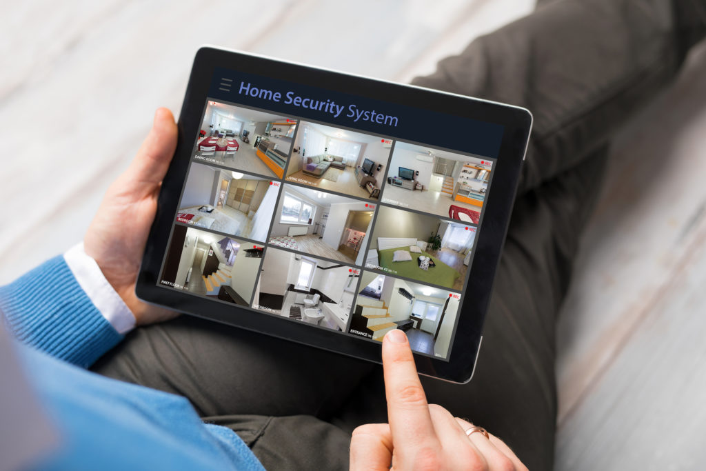 man watching home security cameras on tablet