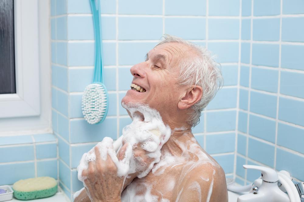 old man taking bubble bath and scrubbing body in walk-in tub