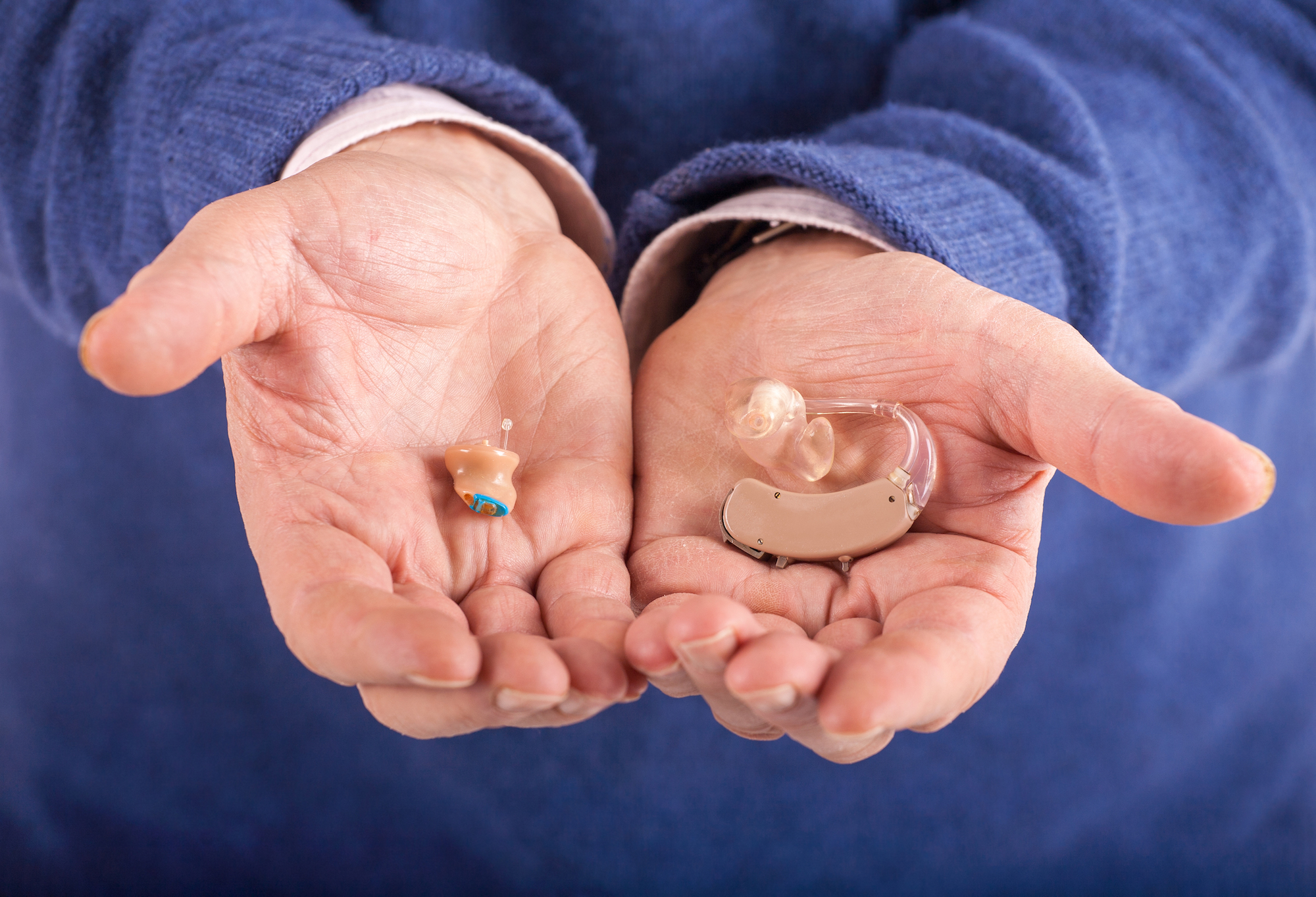 old man's hands showing difference between old school versus modern hearing aids