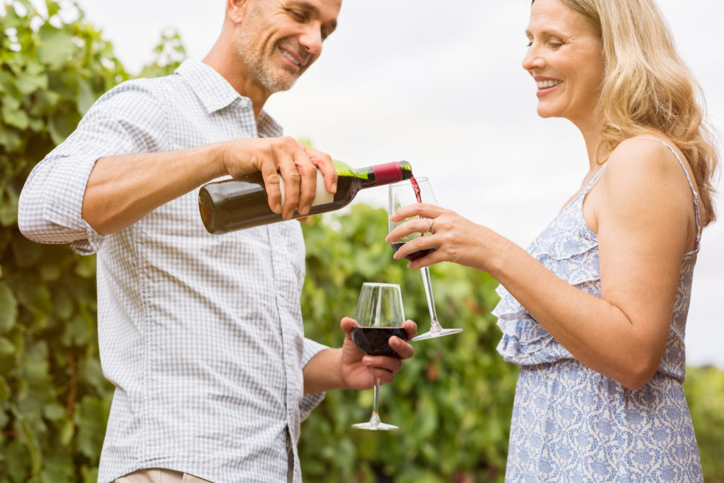 older couple pouring wine in a vineyard as part of a weekend getaway