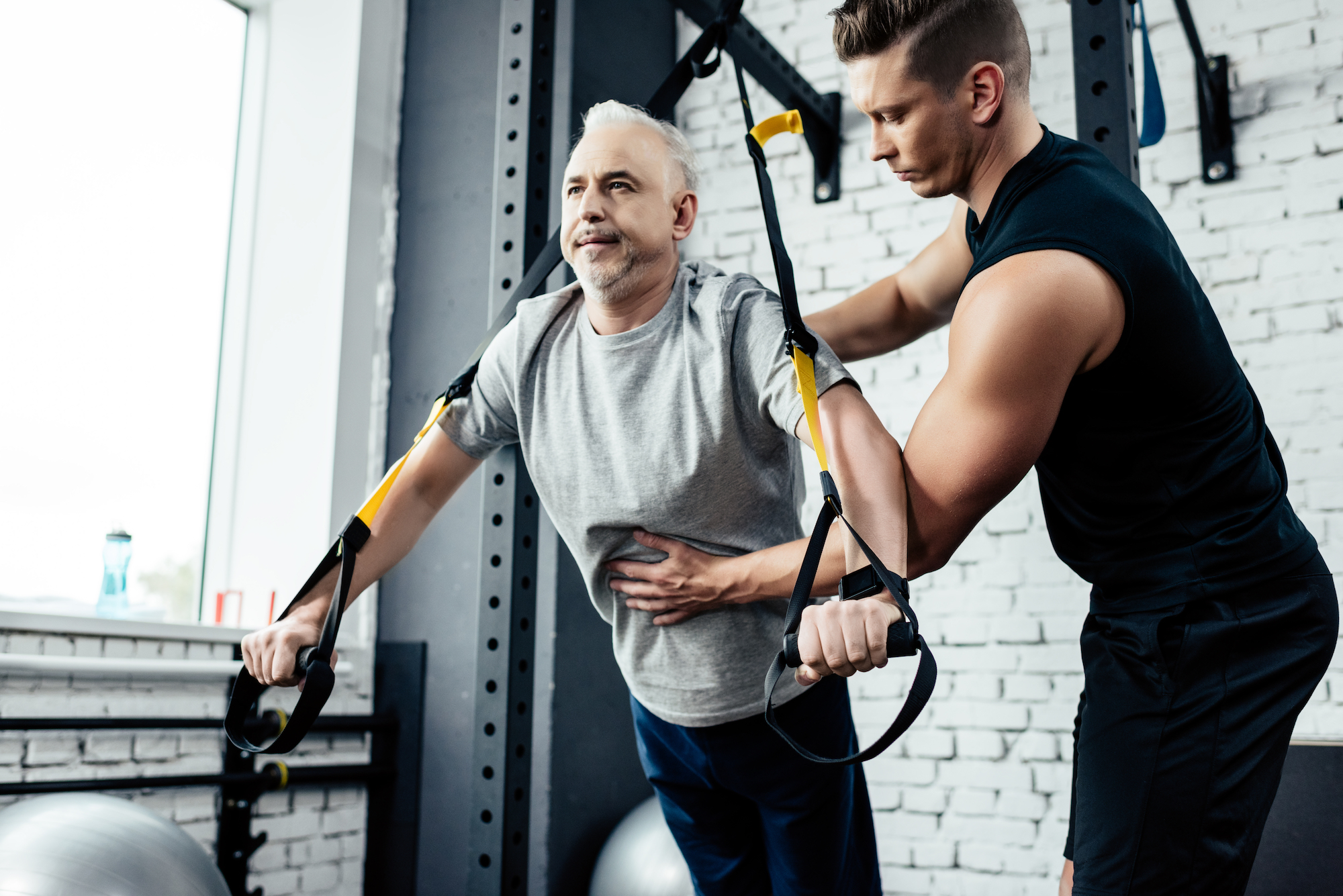 older man with wall mounted resistance bands doing body weight exercises