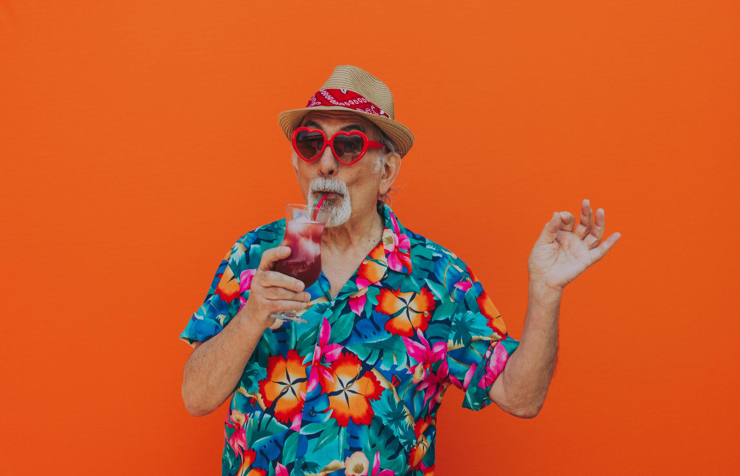 older senior man sipping tropical drink on orange background