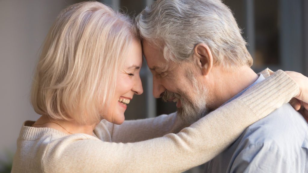 older white couple with grey and platinum blond hair laughing lovingly
