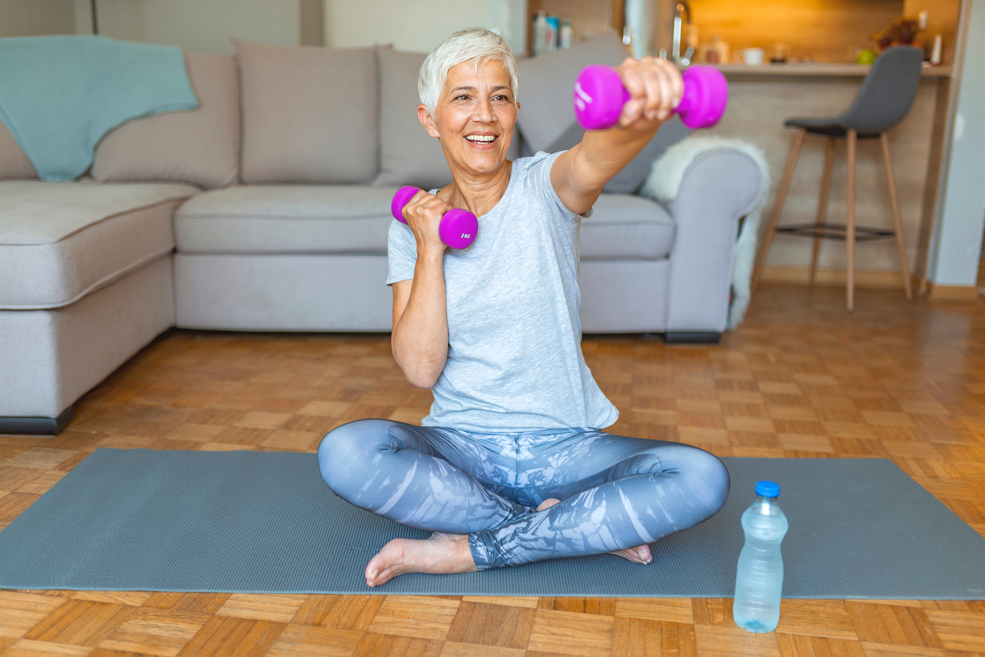older woman lifting pink dumbbells and sitting on a yoga mat
