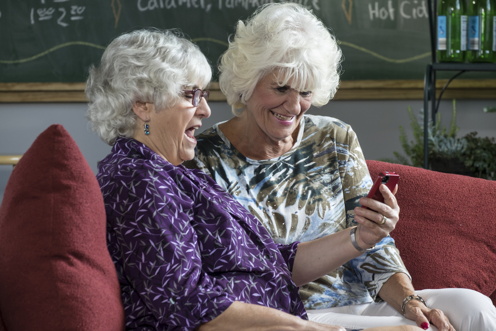 two senior women looking and laughing at a smartphone dating app