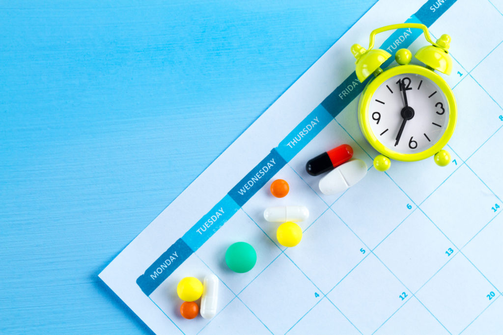 paper calendar with different pills for each day and a small clock
