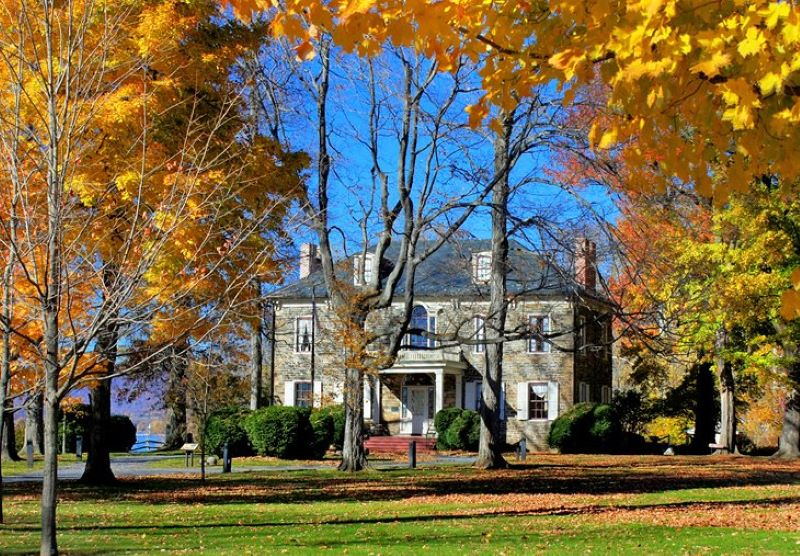 Autumn in Harrisburg featuring a brick  mansion surrounded by trees with bright yellow leaves and a blue sky background