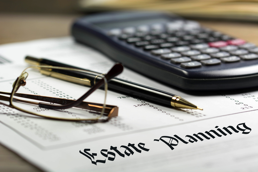 reading glasses, fountain pen, and calculater on document that says estate planning