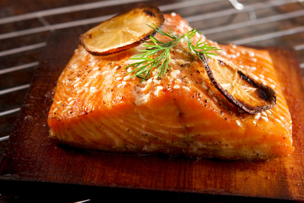 A piece of delicious grilled salmon on a wood plank