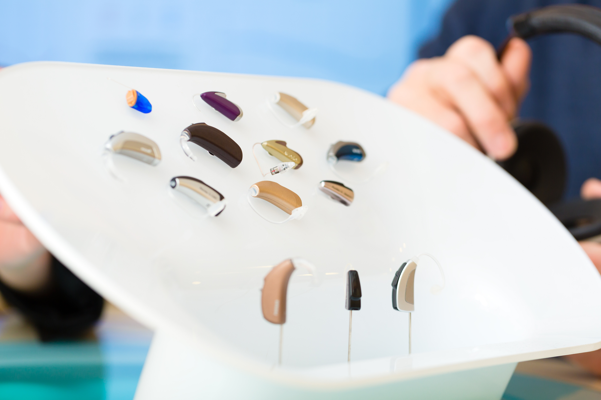 selection of hearing aids in colors and sizes mounted on white board