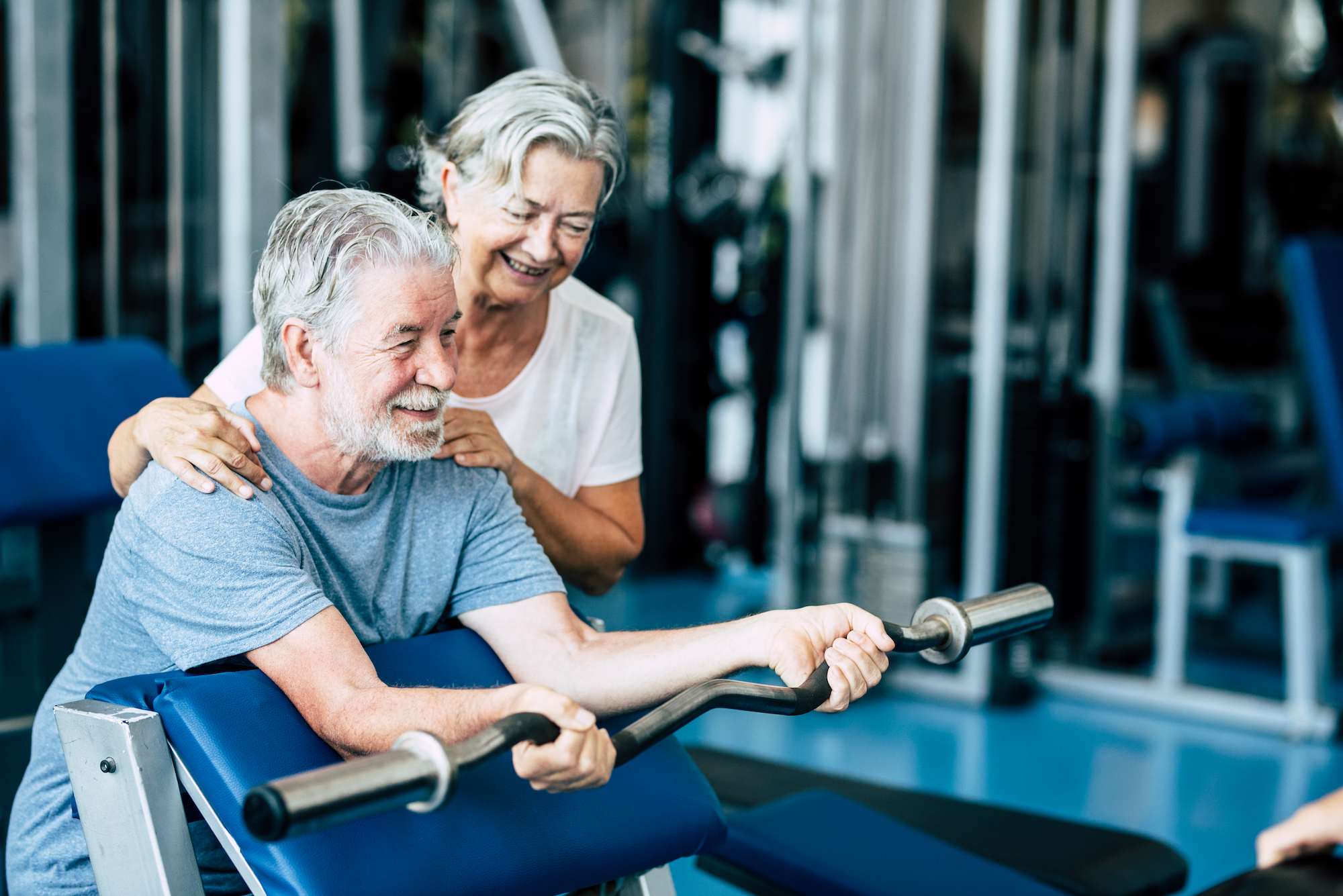 senior couple doing barbell lifts at the gym
