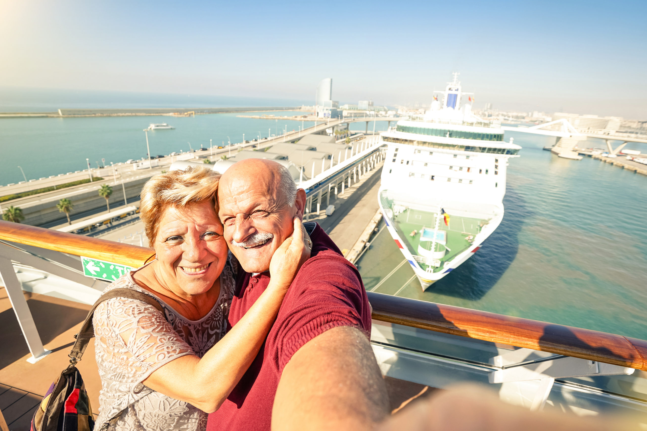 senior couple with cruise ship in the background ready to embark
