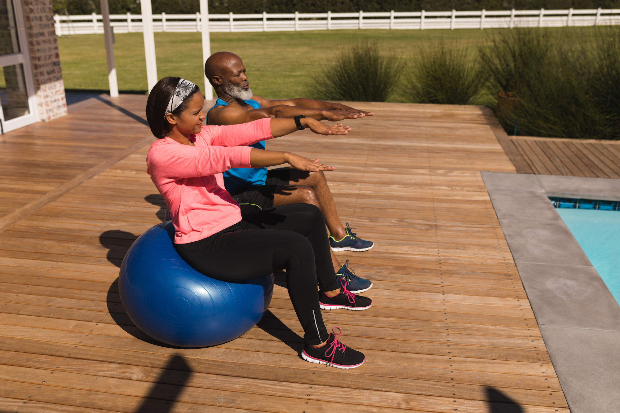 senior couple on exercise ball on deck at home in front of pool