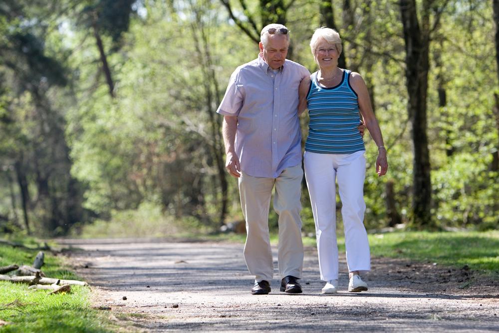 senior couple walking through the park in the daytime