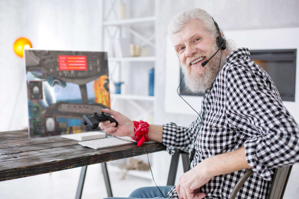 senior man playing simulator on a PC