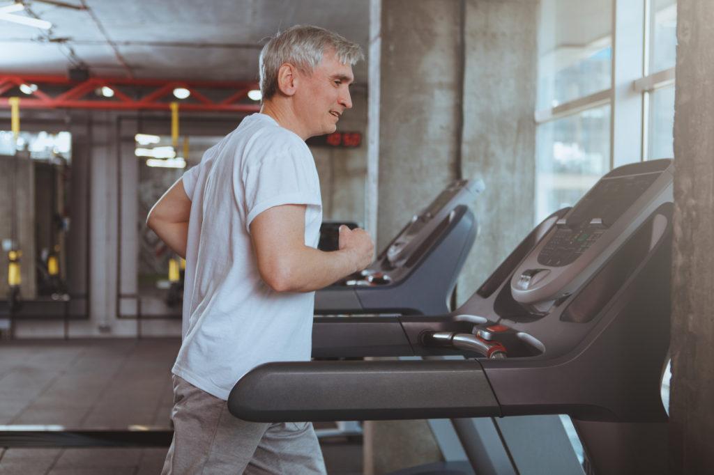 senior man with grey hair running on treadmill