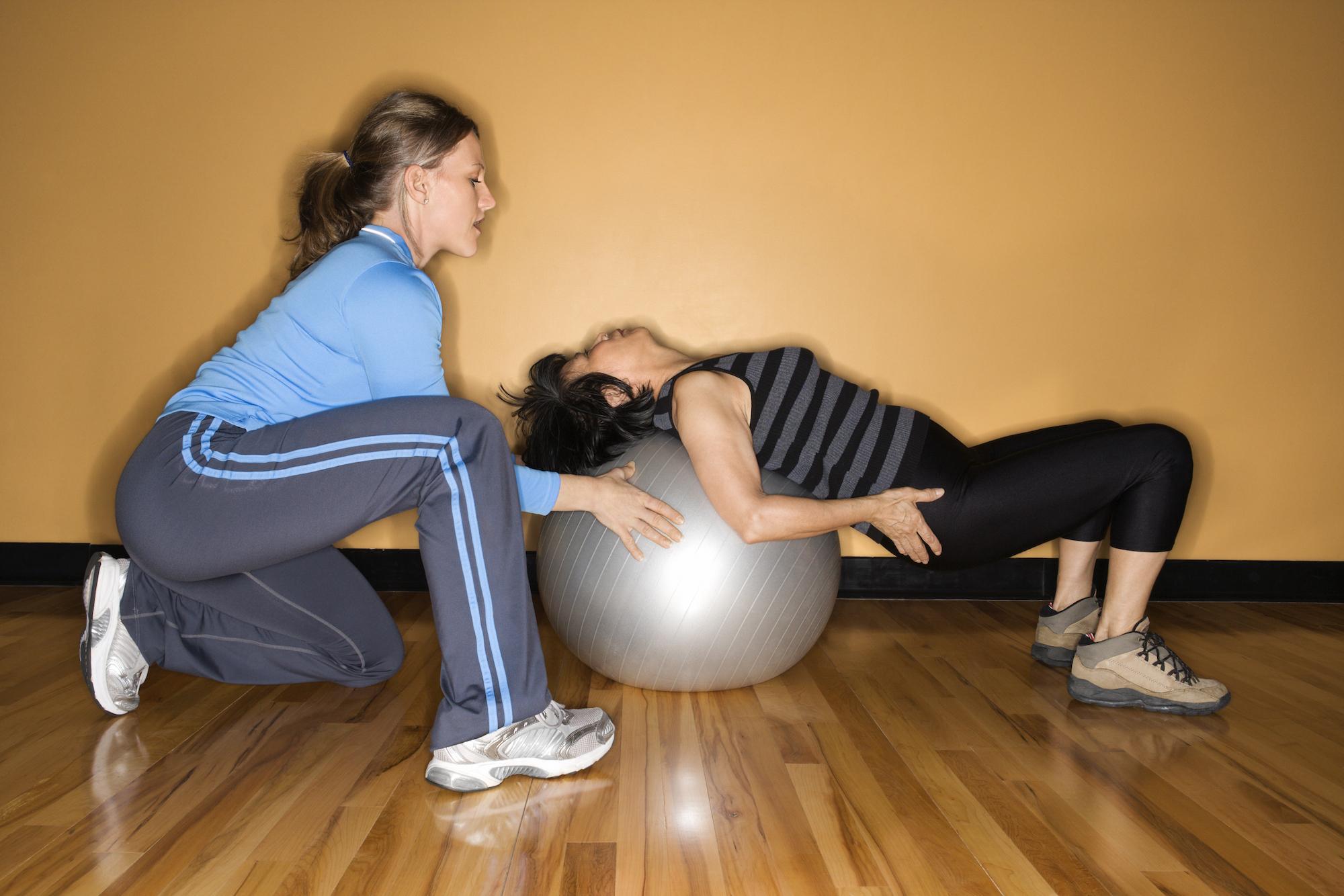 senior woman doing squats on exercise ball