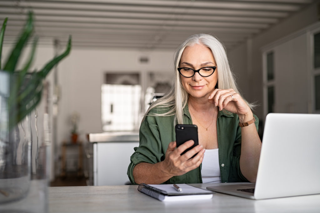 senior woman looking at smartphone with a modern apple laptop on desk