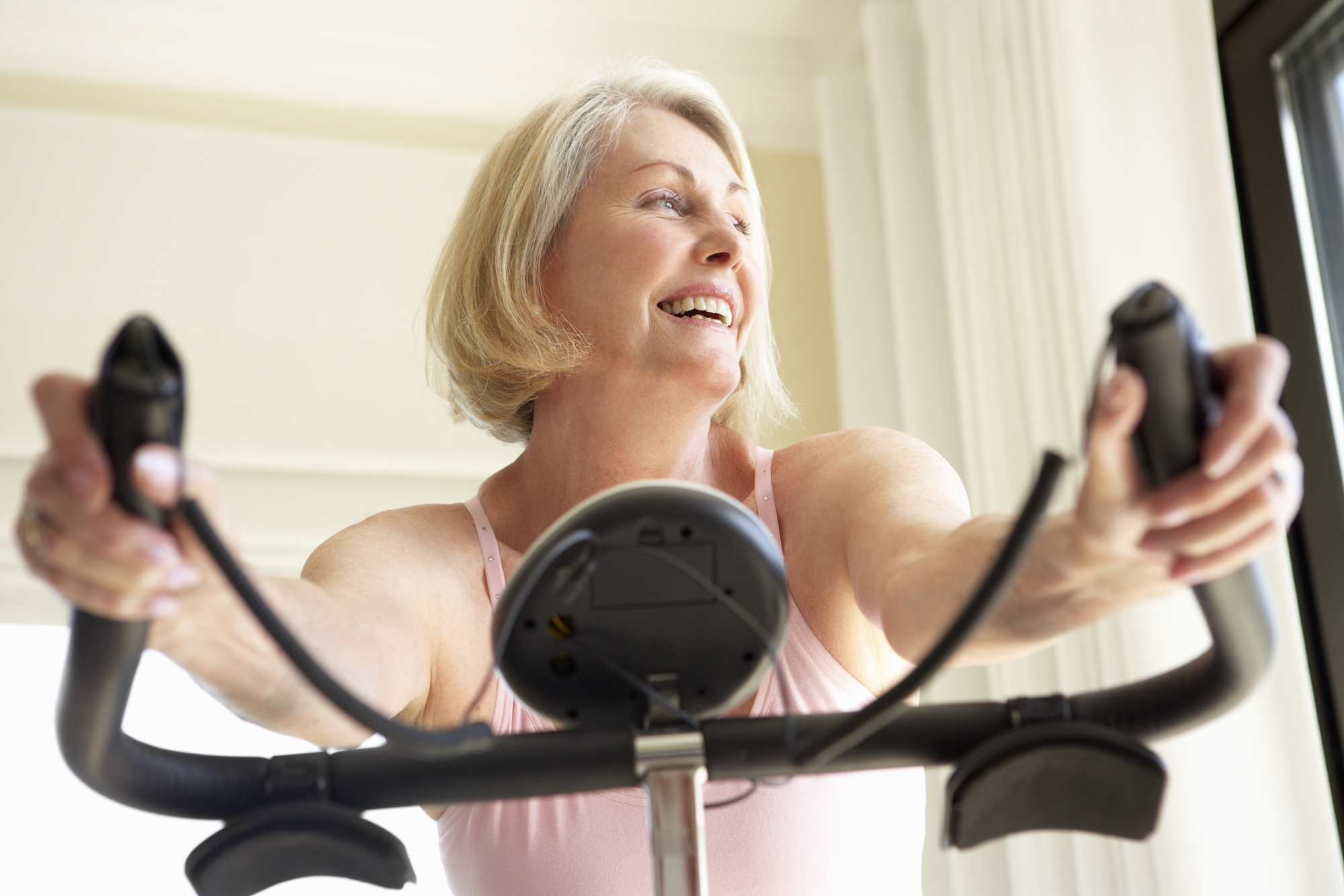 senior woman smiling on exercise bike in her home working out