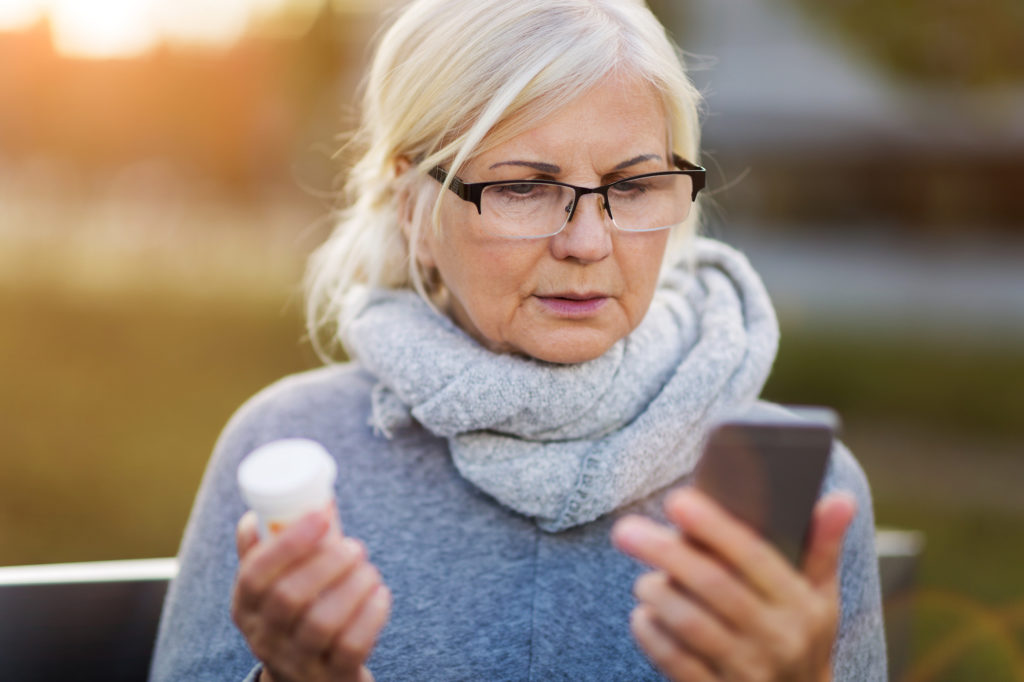senior woman with blond hair and glasses holding a pill bottle and looking at her smartphone