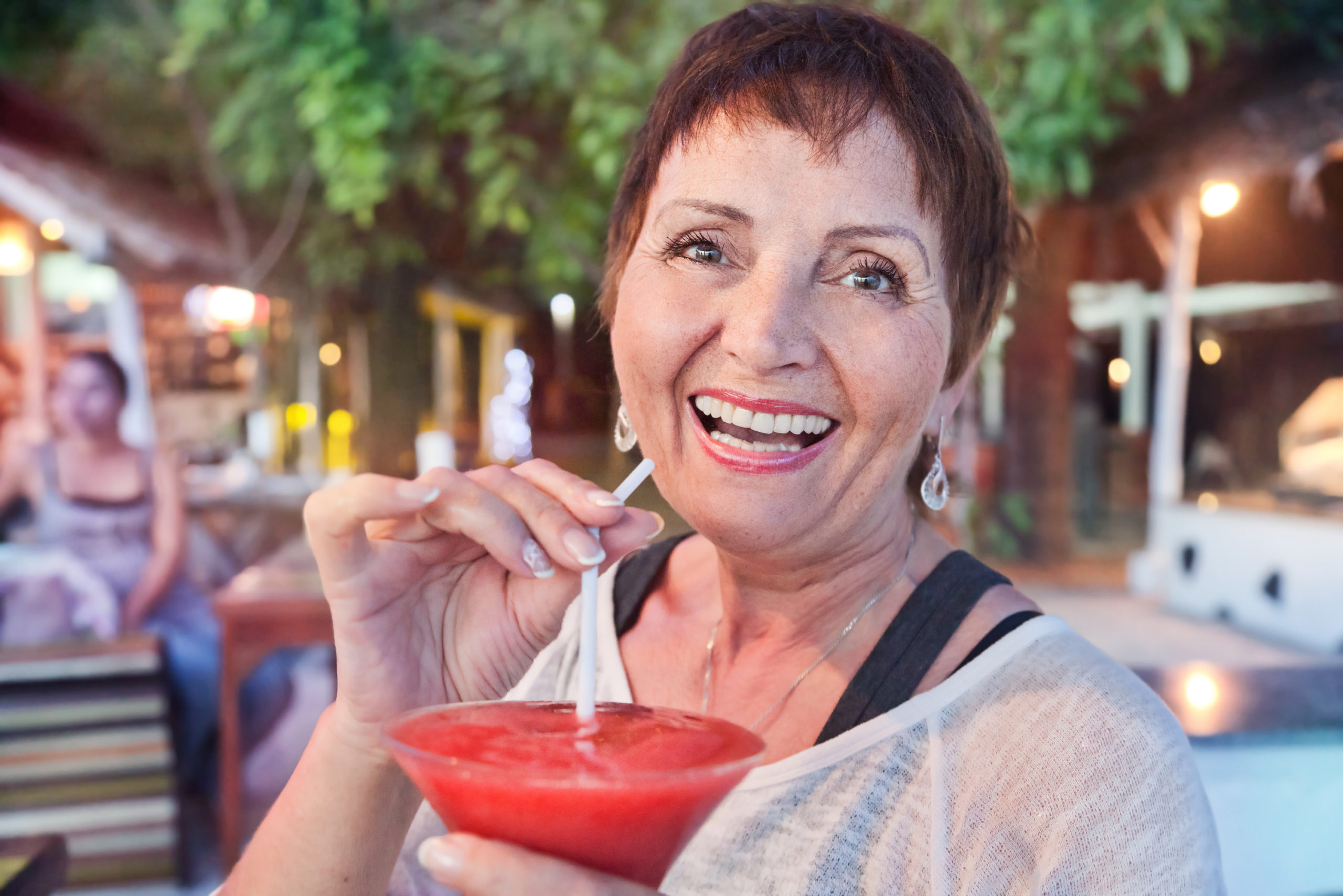 senior woman with short hair drinking frozen margarita on vacation