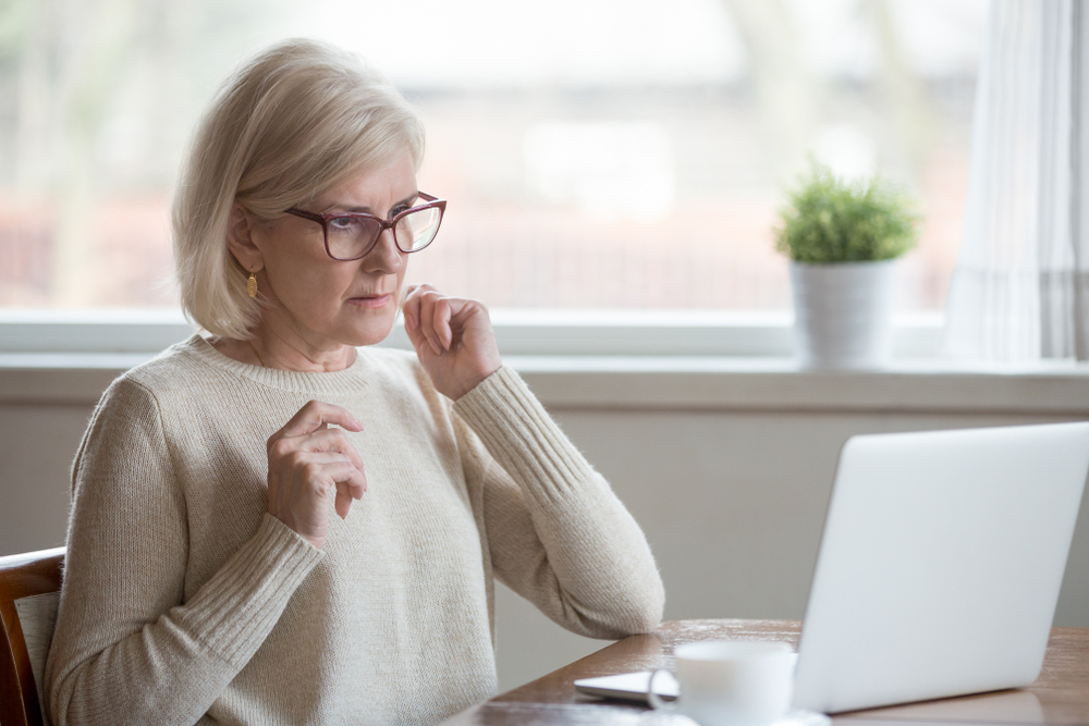 senior woman with worried look at computer screen