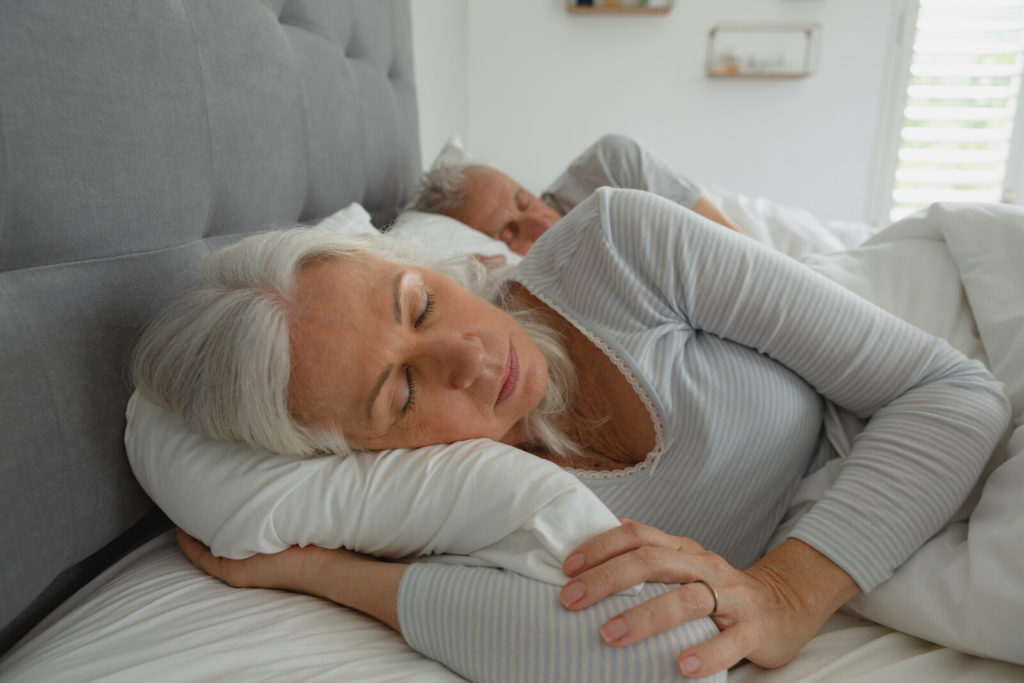 A senior man and woman lie in bed sleeping peacefully.
