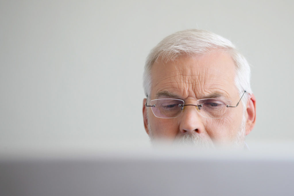 A senior man with glasses on looks at a computer.