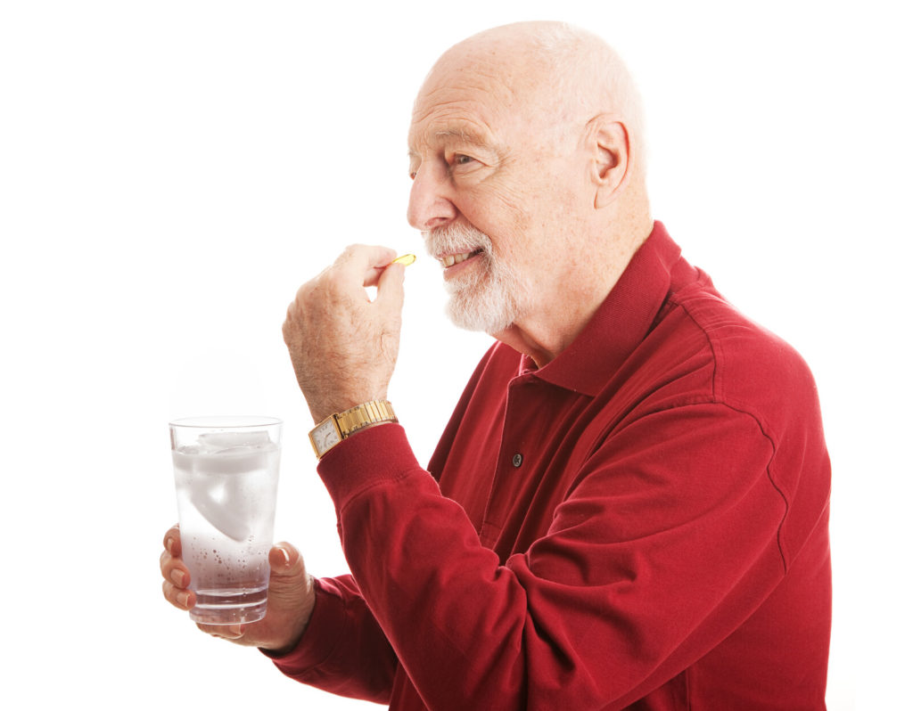 A senior man takes a vitamin with a glass of water.